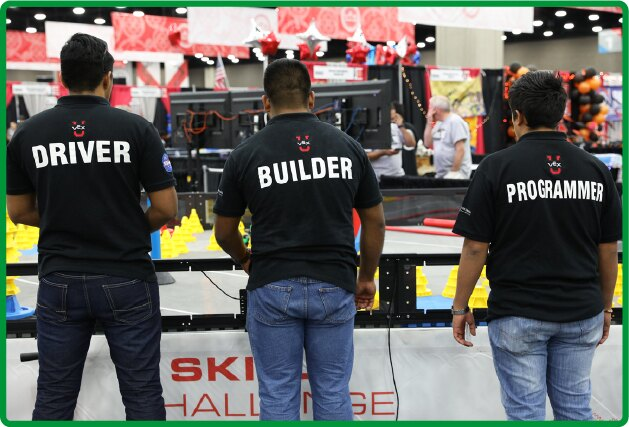 3 collage age students stand in front of a competition field with their backs to the camera. their shirts read: VEX U Driver, builder, and programmer