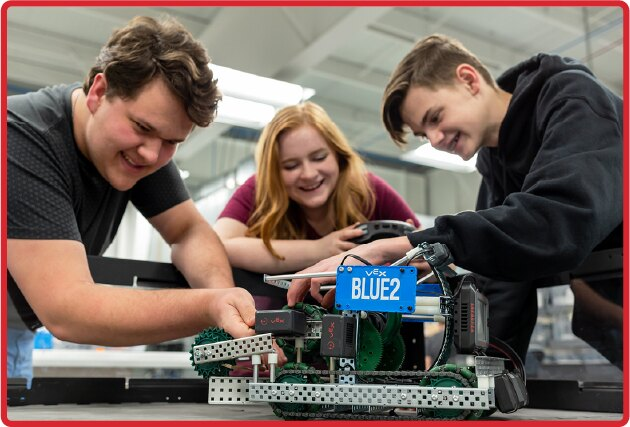 three high school age students work on a V5 robot