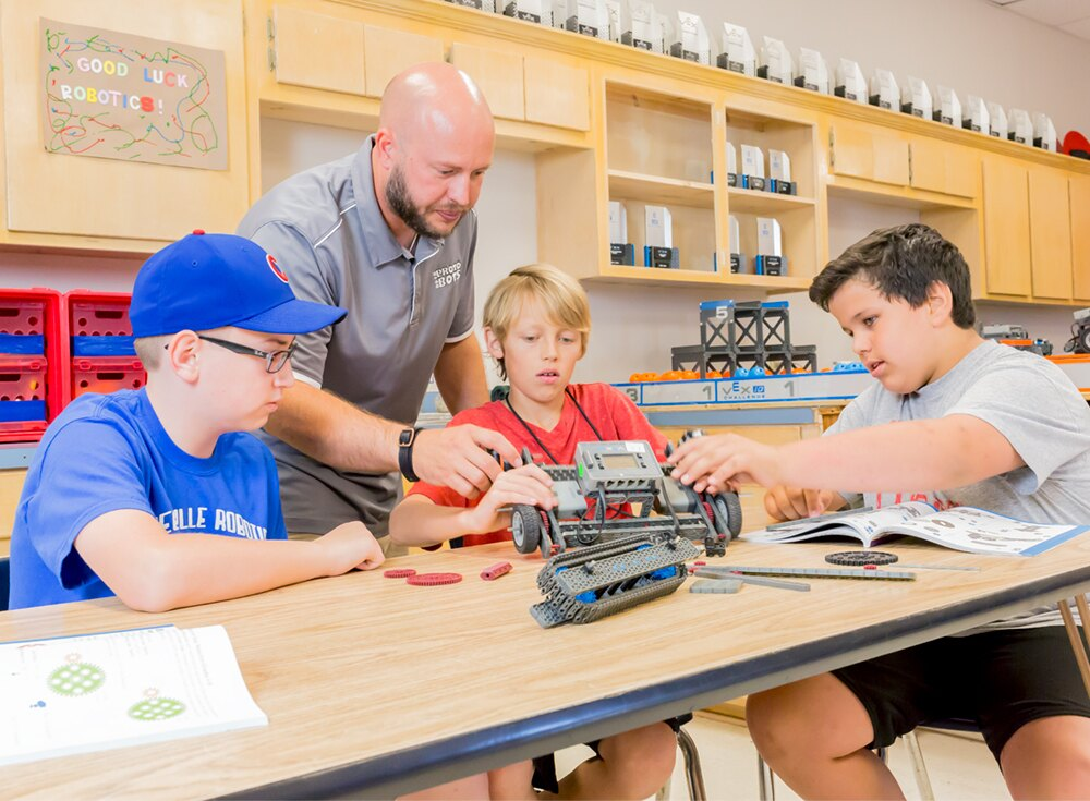 3 students working on a vex IQ robot are assisted by their teacher